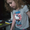 The unedited, colour photograph of my young daughter, wearing a t-shirt and jeans. She's nearly side on, looking down at the floor in front of her.