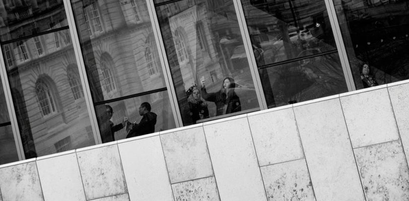 people standing in front of a large window taking photos with phones and cameras. The windows have reflections of the buildings opposite