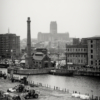 A view over the Albert Dock of the Pump House pub, which has a tall chimney, and in the distance is the cathedral