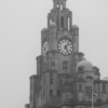 One of the top turrets of the Liver Building with a Liver Bird on top and a clock face.