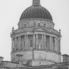 A close up shot of the top tower and dome of the building. It has grand architecture, with columns and tall sash windows