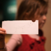 A young girl holds out a piece of paper with an ibis drawn on it