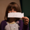 A young girl holds a piece of paper out, partially obscuring her face. She has drawn a rabbit and written 'pet bunny' on it. She has embossed it with a cat