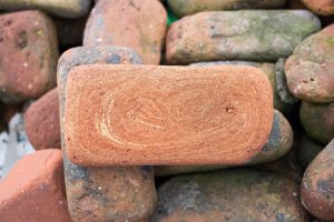 A pile of bricks, all with rounded corners and worn surfaces from being on the beach for decades