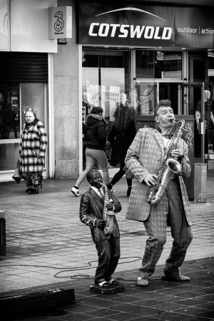 A man dressed in a 1950s-style suit, playing a saxophone. Next to him is a half-sized statue of another man playing the saxophone