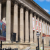Looking diagonally at the hall, which has several huge corinthian columns. Between some of the columns are banners with names listed on them; two men in a cherry picker are changing the banners
