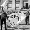 Five men trying to fold up a fabric banner with hand-painted lettering, but the wind is blowing hard. A man and woman stand either side of them with flags in their hands