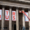 The fourth banner between the columns is being taken down. The first three have the letters 'tr' and 'jus', beginning the spelling out of 'truth' and 'justice'