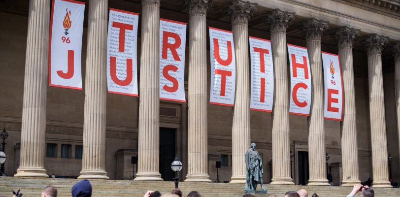 The banners set out between the columns of the hall spelling out 'truth' and 'justice'. People are standing and photographing the scene