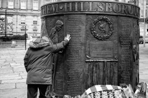 a man stands with his head bowed and his hand placed on the bronze memorial on the list of names of the deceased