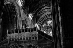 looking up at the back of the cathedral. part of a large stained glass window is at the back. in the foreground is a bridge-like structure with a cross on it