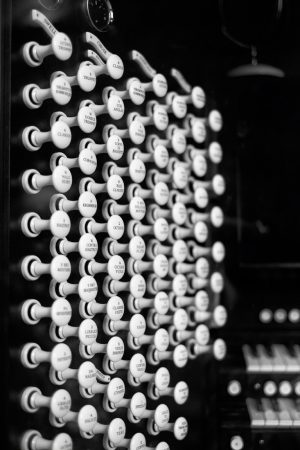several rows of organ stops - small, white levers that are pushed in and pulled out to change the way the organ sounds. there are around 70 stops visible