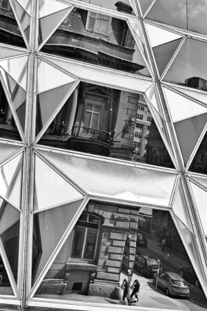 Geometric and angular glass on the side of a building. In the glass, a 19th century building is reflected. The reflection is a little disjointed and broken because of the angular glass