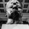 Looking up at a colossal granite head of a pharaoh.
