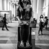 A granite statue of the pharaoh Amenhotep the Third, in the British Museum, with visitors milling around.