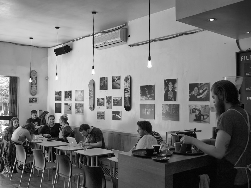 A view of part of the Geoff Rowley photography exhibition in Bold Street Coffee with customers sitting in front of the pictures