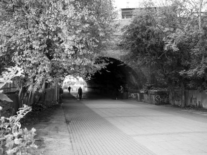 Looking through the Marsh Lane Time Tunnel, with trees overhanging and people walking through