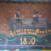 Part of the timeline mural in Marsh Lane Time Tunnel showing two construction workers building a rail track, with the caption 'Liverpool-Bootle rail link 1850'