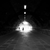 Looking down the Marsh Lane Time Tunnel, to see the silhouette of the busker and an elderly lady with a shopping trolley