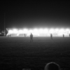A handful of teenagers walking across a playing field, backlit by the lights from the spectator stand behind them