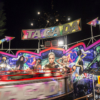 The Tagada ride from the side with the centre blurred by its spinning. Behind the ride a firework is exploding in the sky