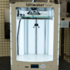 A face-on view of the 3D printer. It's rectangular in shape and open down the front. the printer head is at the top, printing. the object being printed stands on a glass shelf, which moves down the inside of the printer as the object is being printed. The inside of the printer is very bright