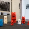 A collection of 3D printed artefacts. There are several lions, ranging in size from around 6 inches tall to less than an inch. There is also a reproduction of a Hathor head. The prints are either red, white or blue in colour.
