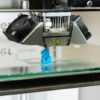 A closeup of the printer head and the lion statue being printed (it's one of the very small ones).