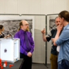 Three men standing next to the 3D printer, talking