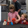 Two young girls, in school uniform, standing next to the table and playing with the 3D-printed lion statues