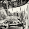 A young girl sitting on a merry-go-round, smiling as she's enjoying the ride