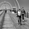 Coming towards the camera, which is looking down the pier, are two teenage girls on skateboards. One of the them is holding a balloon and looking at the floor, the other is looking at the camera