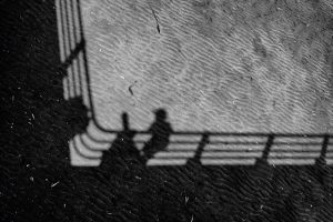 Looking down at the sand directly beneath the pier. The pier is casting a dark shadow on the sand, as a child standing on the pier and a telescope stand