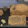 Looking at the artefacts in the centre of the glass display case. There are a couple of larger, stone pieces, one in the shape of a sundisk with cobras on the sides. The other is rectangular with large hieroglyphs inscribed on it. To the left are three fine ceramics and a selection of fragments with hieroglyphs. To the right are a couple more fragments with depictions of cobras.