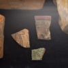 A closeup of three small fragments of ceramics, each with a depiction of a cobra