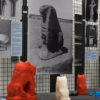 Three of the larger 3D printed lions are facing away from the camera, looking towards one of the photos, which is of a large stone statue of a lion
