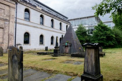 Looking at the pyramid-shaped tomb in the centre of the graveyard. There are other, smaller, more traditionally shaped graves around it. To the left of the photo is the rebuilt St Andrews building