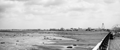 Looking down across an expanse of sand, the buildings of the seafront can be seen on the horizon
