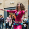 A young woman with long, curly hair, dancing in front of a crowd of people. She's wearing a brightly coloured, tight-fitting, lacey dress with a belt and bra covered in shiny hanging decorative coin-shaped discs. She has her arms outstretched and a big smile on her face