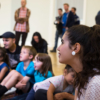 A group of people listening to the storytelling. There are four children and an adult on the floor with a few adults standing behind them. In the foreground is a teenage girl, watching and smiling. The focus is on the teenager with everyone else out of focus
