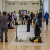A crowd of around twenty people are watching a man, who is about to start painting. He's dressed in black and standing on large sheets of white paper taped to the floor. He holds a paintbrush, which is attached to an extension pole. He's looking at the crowd, slightly bent over, and smiling