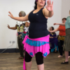 A woman is taking a dance workshop. She's standing with arms out to the side, and is looking back at the other women in the room behind her