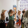 A group of mostly women in a room taking part in a dance workshop. There's ten people in the photo. They're stepping forward with their hands up towards their faces