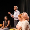 Closeup of a middle-aged man talking to an out-of-shot audience. There are four women sitting to the side of him