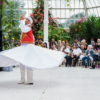 An Egyptian whirling dervish dancer. He wears a white costume with a red and gold waistcoat and is mid-spin.
