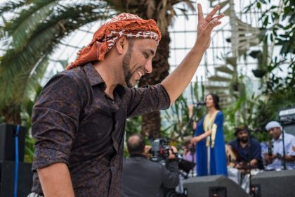 The top half of a man wearing a traditional Arabic head-wrap, with his hand in the air and a smile on his face as he dances to the music from a band in the background