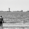 A man on a beach, standing at the edge of the sea with his back to the camera. He's holding his shoes in his hand. Three ships are sailing across the horizon.