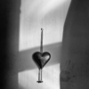 A metal heart - a household decoration - hanging on a chain on a wall. The wall is in shadow except for a large rectangle, where the sun is shining through the window.