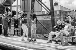 Two teenage girls on a train platform. One of them is dancing. There are other people standing nearby.