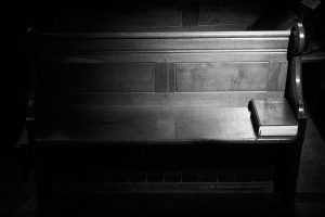 A wooden pew in partial darkness. In the part where the light is shining is a copy of the Bible